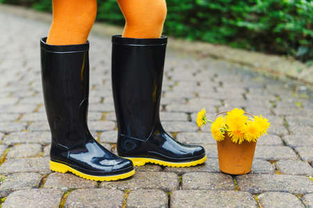 rain boots: Botas de lluvia negras en los pies de un ni�o Foto de archivo