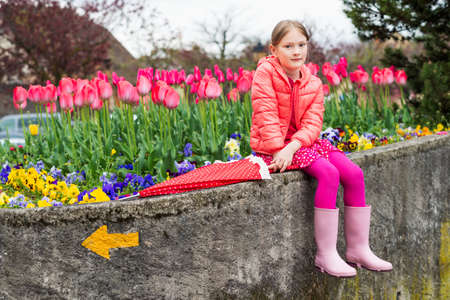 tights: Outdoor portrait of a cute little girl of 7 years old wearing bright pink jacket holding umbrella