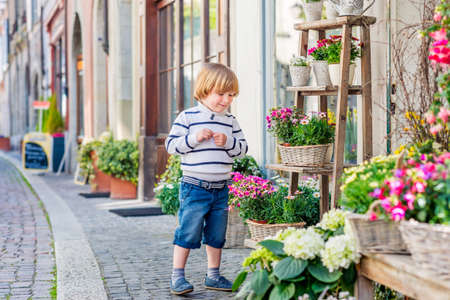 shop tender: Outdoor portrait of a cute little boy playing with flowers in front of a flower shop
