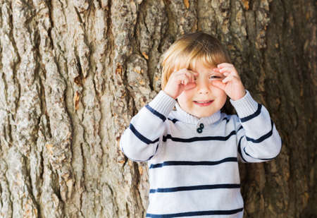 4 year old: Little 4 year old blond caucasian boy in front of an old and massive tree pretending to take a picture with his hands. Stock Photo