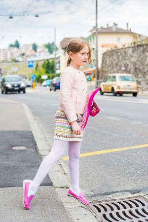 핑크 신발 스커트와 재킷을 입고 도시에서 귀여운 소녀의 패션 초상화