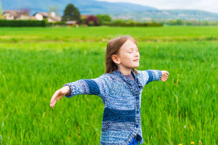 knitted jacket: Adorable little girl playing in field with the wind arms open wide wearing blue knitted jacket Stock Photo