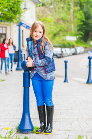 Outdoor portrait of a cute little girl of 7 years old in a city wearing blue clothes and black rain boots