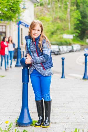 botas de lluvia: Retrato al aire libre de una linda niña de 7 años de edad en una ciudad que llevaba ropa azul y botas de lluvia negras