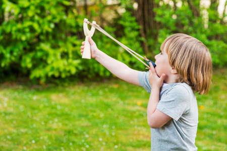 Schattige kleine jongen spelen met katapult buitenshuis