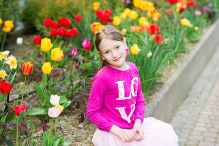 top 7: Outdoor portrait of a cute little girl of 7 years old wearing bright pink top sitting next to flowerbed full of tulips