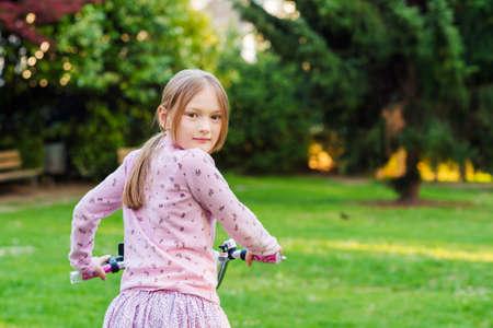 Niña dulce en su bicicleta en un parque mirando hacia atrás por encima del hombro