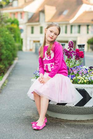 Fashion portrait of a cute little girl of 7 years old wearing bright pink top tutu skirt and ballerina shoes