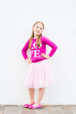 ballerina shoes: Fashion portrait of a cute little girl of 7 years old wearing bright pink tshirt tutu skirt and ballerina shoes posing outdoors against white wall