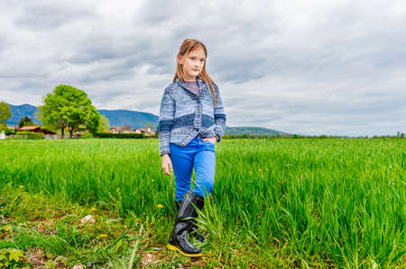 knitted jacket: Fashion portrait of cute little girl of 7 years old wearing blue trousers knitted jacket and black rain boots Stock Photo