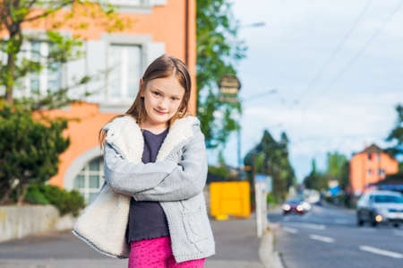 knitted jacket: Outdoor portrait of a cute little girl in a city wearing warm grey knitted jacket standing next to the road Stock Photo
