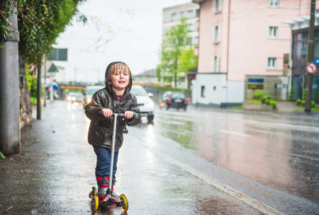the lovely boy: Cute little boy in a very wet clothes on the scooter next to road under the rain Stock Photo