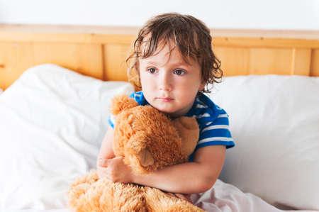 cama: Lindo muchacho del ni�o descansando en una cama con el oso de peluche