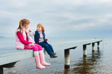 Schattige kinderen spelen bij het meer rusten op een pier