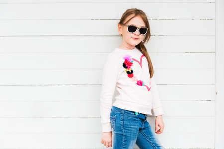 Fashion portret van een schattig klein meisje tegen een witte achtergrond dragen sweatshirt en jeans