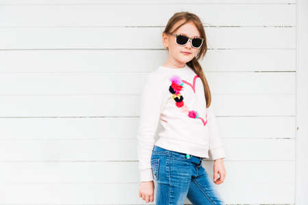 Fashion portrait of a cute little girl against white background wearing sweatshirt and jeans