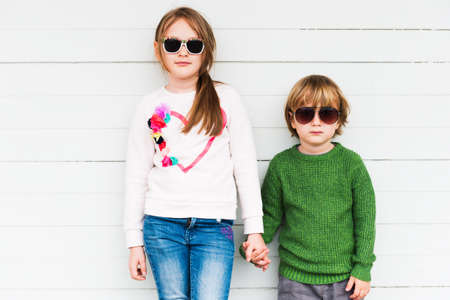 girl friends: Fashion kids outdoors wearing pullovers and sunglasses