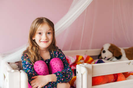 Interior portrait of a cute little girl in her room photo