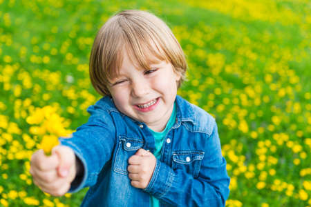 flowers boy: Cute little boy playing with flowers outdoors Stock Photo