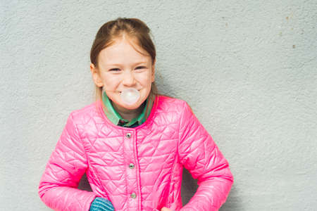 chewing: Portrait of a cute little girl with chewing gum wearing bright pink jacket