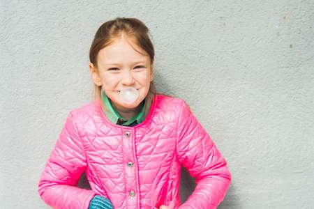 goma de mascar: Retrato de una niña linda con la goma de mascar llevaba chaqueta de color rosa brillante