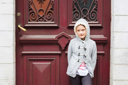 knitted jacket: Outdoor portrait of a cute little girl in a city wearing grey knitted jacket