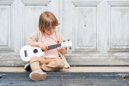 Little happy boy plays his guitar or ukulele, sitting by the wooden door outdoors Stock Photo
