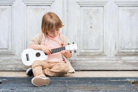 gitara: Trochę szczęśliwy chłopiec gra na gitarze lub ukulele, siedząc przez drzwi drewnianych na zewnątrz pomieszczeń Zdjęcie Seryjne
