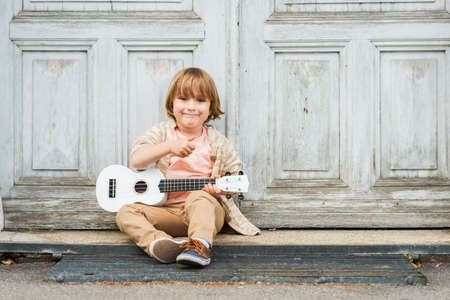 Little happy boy plays his guitar or ukulele, sitting by the wooden door outdoors Archivio Fotografico