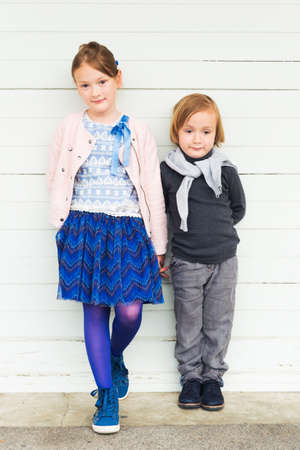 blue grey coat: Two fashion kids against white wooden wall