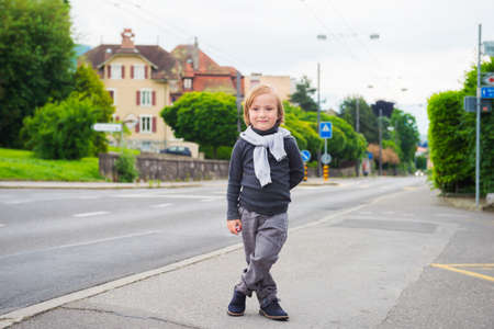 stylish boy: Outdoor portrait of a cute fashion boy in the street, wearing, grey clothes and dark blue shoes