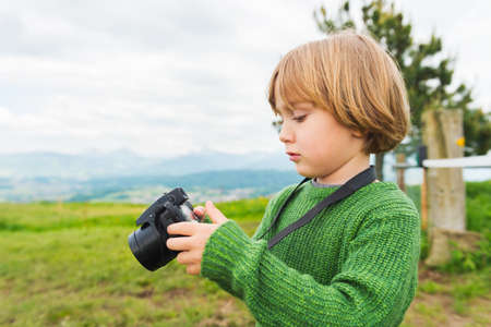 nature photo: Cute little boy taking pictures with a camera