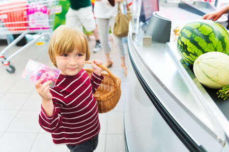 produce departments: Little boy buying fruits in a food store