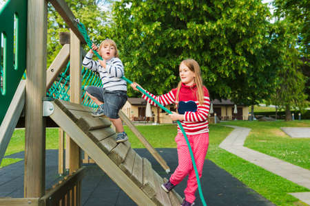 pullovers: Cute kids having fun on playground, wearing warm pullovers Stock Photo