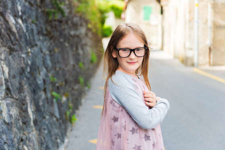 one little girl: Outdoor portrait of a cute little girl in a city, wearing eyeglasses and dress Stock Photo