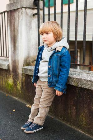 Fashion portrait of adorable little boy wearing denim jacket, beige corduroy trousers, gray sweatshirt and blue shoes