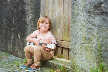 instrumentos de musica: El niño pequeño feliz toca su guitarra o ukelele, sentado junto a la puerta de madera al aire libre