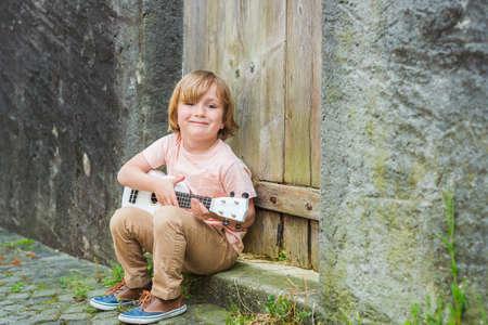 instruments de musique: Petit garçon heureux joue de la guitare ou ukulélé, assis près de la porte en bois en plein air