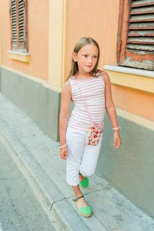 mignonne petite fille: Outdoor portrait d'un joli mode petite fille qui porte un pantalon blanc et des chaussures vertes