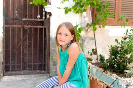 mignonne petite fille: Portrait d'une petite fille mignonne se reposant dans une vieille ville typiquement italien