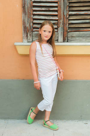girl shoes: Outdoor portrait of a cute fashion little girl wearing white trousers and green shoes