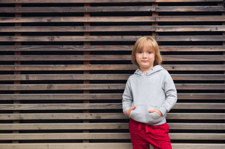 handsome boy: Fashion portrait of adorable toddler boy wearing grey sweatshirt and red trainings, standing against wooden background