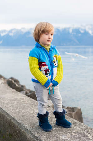 knitted jacket: Winter portrait of a cute little boy, wearing funny warm knitted jacket with snowman, standing next to lake against mountains
