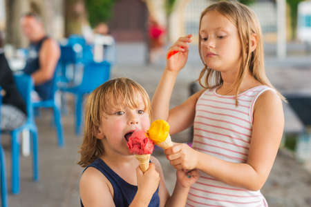 ice cream woman: Portrait of two adorable kids eating colorful ice cream outdoors Stock Photo