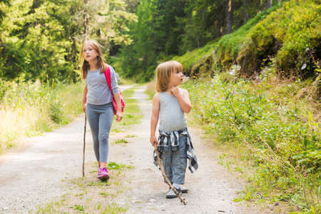 Two cute kids hiking in forest Archivio Fotografico