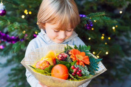 boy standing: Portrait of a cute little boy holding christmas flower bouquet, standing next to christmas tree