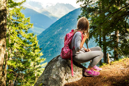 Cute little girl hiking in swiss Alps, resting on a rock and admire amazing view