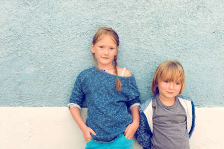 stylish man: Two kids, girl and little boy, posing outdoors, standing against blue wall, toned image, instagram effect Stock Photo