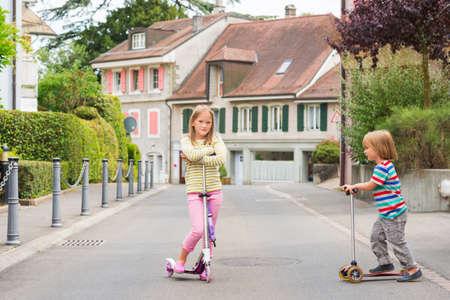 nene y nena: Dos niños lindos jugando al aire libre, scooters de equitación Foto de archivo