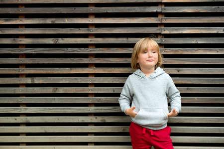 sudadera: Retrato de adorable ni�o peque�o que llevaba la camiseta y rojas entrenamientos gris, de pie contra el fondo de madera